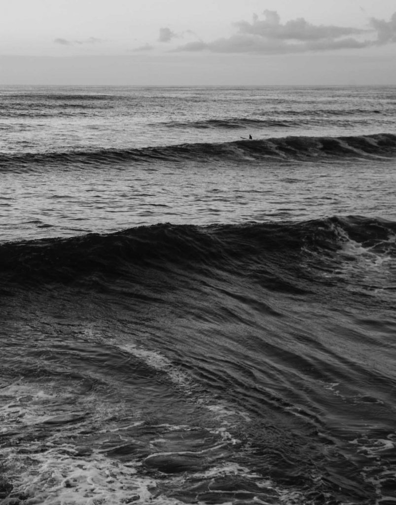 Black and white photograph of the ocean with a lone surfer on the horizon