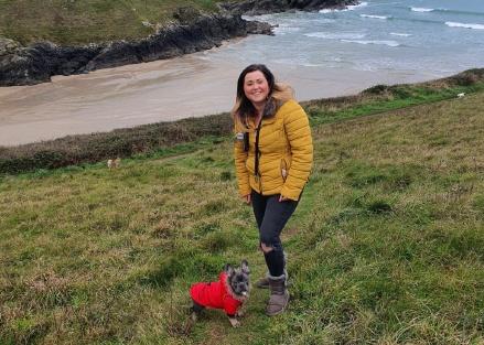 Photo of Jenny Pring enjoying a coastal walk with her dog, Otis
